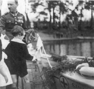 """5-letni Mirosław Szypowski, w towarzystwie ojca, ppłk. Jana, pełni rolę ojca chrzestnego motoróki """"Samarytanka"""" na Jeziorze Rejów w Skarżysku. Lato 1935 r."""