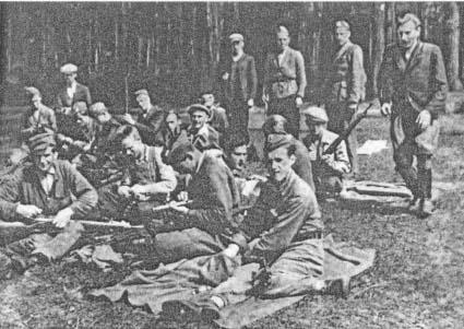 """1 drużyna 3 kompanii 4 pp Leg. podczas czyszczenia broni. Pierwszy od lewej siedzący z karabinem """"Nida"""" Edmund Neyman, zginął 21.08.1944 w bitwie pod Antoniowem."""