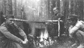 """Wrzesień 1944 r., lasy koneckie. Przy ognisku od lewej: """"Baca"""",  """"Wyżerko"""" (stoi), """"Jerzy"""" i """"Tudor""""."""