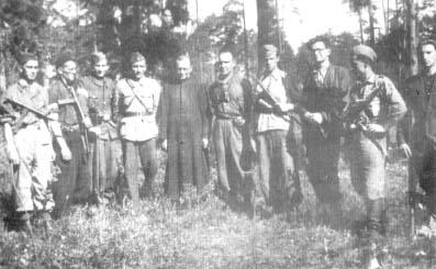 """Żołnierze 27 pp z ks. kapelanem """"Gedyminem"""" (NN), w środku na lewo por. """"Łoś"""" (Henryk Szopiński) na prawo ppor. """"Leon"""" (Edward Kozłowski)."""