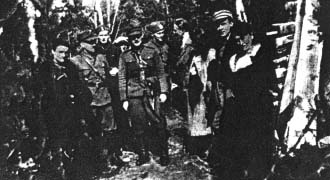 """W obozowisku leśnym """"Gorgoń"""" Obwód Radomsko oddziału partyzanckiego  por. """"Andrzeja"""" (Floriana Budniaka). Stoją od lewej: łączniczka """"Małgorzata"""" (Jadwiga Bielawska), por. """"Andrzej"""" (Florian Budniak), ppor. """"Robotnik"""" (Bronisław Skóra-Skoczyński), łącznik """"Woda"""" (NN), ppor. """"Postrach"""" (Jan Kaleta), sierż. """"Lis"""" (Janusz Ojrzyński), pchor. """"Kłos"""" (Stefan Siemiński), łączniczka """"Jadzia"""" (NN),  pchor. """"Franek"""" (Stefan Jedynak), Wacława Orłowska referentka WSK."""