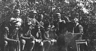 """Żołnierze 2 kompanii 74 pp przy ognisku. Siedzą od lewej: """"Zbyszek"""" (Władysław Mozdeń), """"Biały"""" (Antoni Jędryszek), """"Drągal"""" (Józef Schlinke), """"Szczupak"""" (NN), ppor. """"Uparty"""" (Teofil Baryła). Stoją od lewej: """"Nietoperz"""" (Kosiński), """"Wiktor"""" (Kuraś-Krasicki), ppor. """"Marek"""" (Tomasz Buliński), """"Sokół"""" (Tadeusz Kromski), """"Równy"""" (Jerzy Bartnik)."""