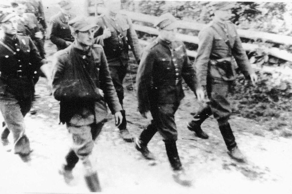 """Pogrzeb por. cc Jana Piwnika """"Ponurego"""" 17 czerwca 1944 roku. Idą od prawej: cc kpt. Stanisław Sędziak """"Warta"""", ppłk Prawdzic-Szlaski """"Borsuk"""", por. Bojomir Tworzyański """"Ostoja"""", cc por. Jan Woźniak """"Kwaśny""""."""